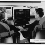 Photographic copy of photograph, 1970 (original photograph in STRATCOM Historian files, Offutt AFB, Bellevue, Nebraska). Interior view of two crew members operating the data display system in the battle staff compartment. - Offutt Air Force Base, Looking Glass Airborne Command Post, Looking Glass Aircraft, On Operational Apron covering northeast half of Project Looking Glass Historic District, Bellevue, Sarpy County, NE Photos from Survey HAER NE-9-B